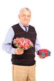 Homme mûr retenant le cadeau et le bouquet des fleurs Image libre de droits