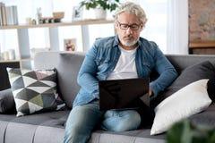 Homme mûr sûr à l'aide de l'ordinateur à la maison Image libre de droits