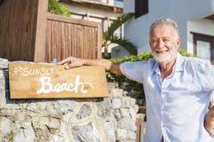 Homme mûr se tenant prêt un signe de station de vacances Photos stock