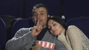 Homme mûr shushing à l'appareil-photo warching un film au cinéma photo stock