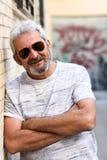 Homme mûr souriant avec des lunettes de soleil d'aviateur à l'arrière-plan urbain Photo libre de droits
