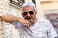 Homme mûr souriant avec des lunettes de soleil d'aviateur à l'arrière-plan urbain Photo stock