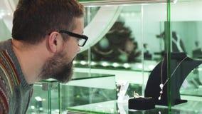 Homme mûr souriant pendant argenté gaiement de examen au magasin de bijoux banque de vidéos
