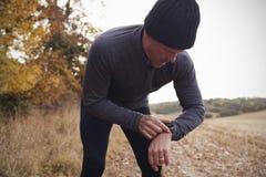 Homme mûr sur le traqueur d'activité d'Autumn Run Around Field Checks Photos libres de droits