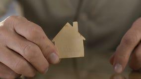 Homme mûr tenant la figure en bois de la maison avant caméra, manquant à la maison dans l'hospice banque de vidéos