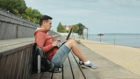 Homme mûr, touriste à l'aide d'un ordinateur portable, se reposant sur la plage sur un banc en bois banque de vidéos