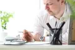 Homme mûr travaillant avec la calculatrice évaluant des occasions financières pour des vacances de famille photos stock
