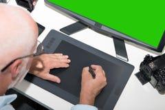 Homme mûr travaillant avec la tablette graphique dans le bureau images stock