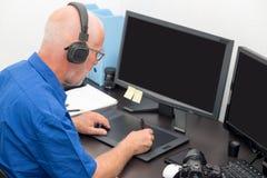 Homme mûr travaillant avec la tablette graphique dans son bureau images stock