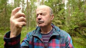 Homme mûr utilisant le jet d'insectifuge de moustique ou clips vidéos