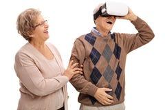 Homme mûr à l'aide du casque de VR avec la femme tenant sa main Image libre de droits