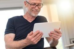 Homme mûr à l'aide du comprimé numérique, effet de la lumière Photographie stock