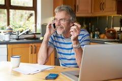 Homme mûr à l'aide du téléphone portable regardant à la maison des finances Photographie stock