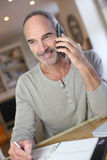 Homme mûr à la maison parlant sur le smartphone Image libre de droits