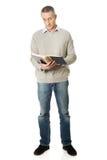 Homme mûr affichant un livre Photographie stock libre de droits