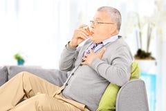 Homme mûr assis sur un sofa prenant le traitement d'asthme à la maison Photos stock