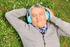 Homme mûr avec des écouteurs se trouvant sur l'herbe image stock