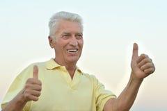 Homme mûr avec des pouces  Photo stock