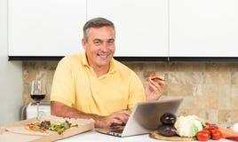 Homme mûr avec l'ordinateur portable dans la cuisine Image stock