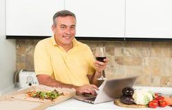 Homme mûr avec l'ordinateur portable dans la cuisine Photo stock
