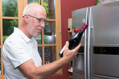 Homme mûr avec la bouteille de vin rouge, sur la cuisine Images libres de droits