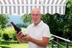 Homme mûr avec la bouteille de vin rouge, sur la terrasse Photographie stock
