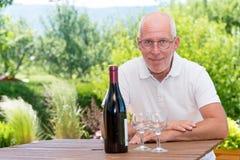Homme mûr avec la bouteille de vin rouge, sur la terrasse Images libres de droits