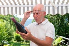 Homme mûr avec la bouteille de vin rouge, sur la terrasse Photo stock