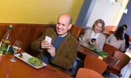 Homme mûr avec le mobile à la table en café Photographie stock libre de droits