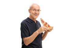 Homme mûr ayant une tranche de pizza Photographie stock libre de droits