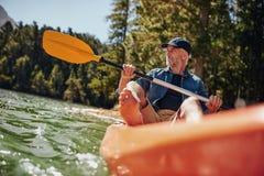 Homme mûr barbotant un kayak Photo stock