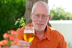 Homme mûr buvant d'une bière dehors Image stock