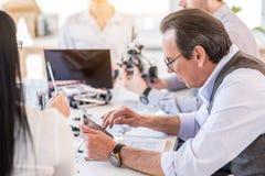 Homme mûr concentré travaillant avec son équipe dans le bureau photo libre de droits