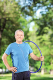 Homme mûr convenable tenant un hulahoop en parc Photographie stock
