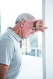 Homme mûr déprimé se penchant sur le mur Image libre de droits