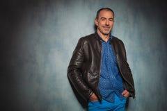 Homme mûr dans la veste en cuir se tenant dans le studio gris Images stock
