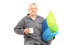 Homme mûr dans les chemises de nuit tenant une tasse et un oreiller de café Image stock