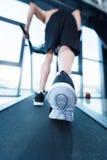 Homme mûr dans les vêtements de sport s'exerçant sur le tapis roulant dans le gymnase Photo libre de droits