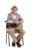 Homme mûr dans une chaise d'école prenant des notes Photographie stock