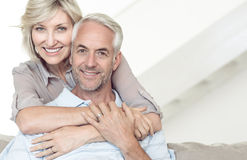 Homme mûr de embrassement de sourire de femme par derrière sur le sofa photos libres de droits
