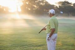 Homme mûr de golfeur se tenant sur le champ Image stock