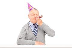 Homme mûr de joyeux anniversaire avec le soufflement de chapeau de partie Images stock