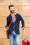 Homme mûr de sourire se tenant dehors avec le sac et le téléphone portable Image stock