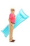 Homme mûr des vacances tenant un matelas de natation Photos stock