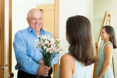 Homme mûr donnant des fleurs à la femme Photo stock