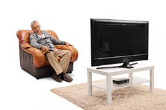 Homme mûr dormant devant la TV Photos stock