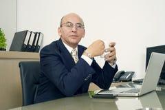Homme mûr en café potable de formalwear tout en se reposant à son lieu de travail Images stock