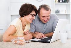 Homme mûr et femme regardant l'ordinateur portable Photographie stock
