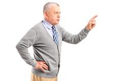 Homme mûr fâché se dirigeant avec le doigt et menaçant Image libre de droits