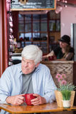 Homme mûr grincheux dans le café Images libres de droits